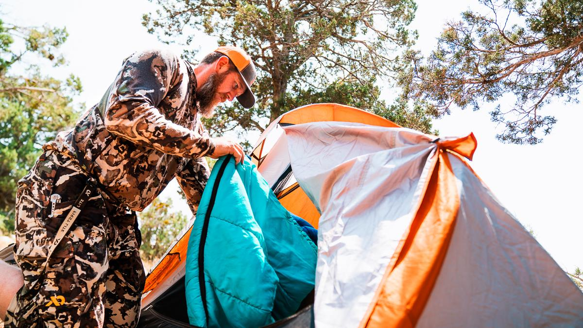 Hunter putting sleeping bag into shelter